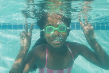 peace sign: Cute kid posing underwater in pool at the leisure center