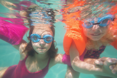 armbands: Cute kids posing underwater in pool at the leisure center Stock Photo