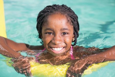 レジャー センターでプールで泳ぐかわいい女の子