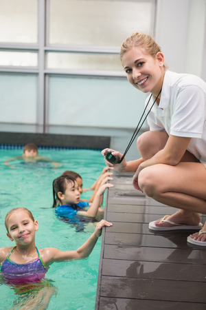 asian teacher: Pretty swimming coach smiling at camera at the leisure center