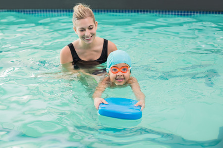 swimming pool float: Cute little boy learning to swim with coach at the leisure center