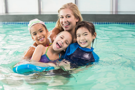 swimming pool woman: Cute swimming class in pool with coach at the leisure center Stock Photo