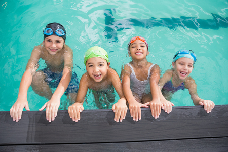 swim goggles: Cute swimming class in the pool at the leisure center Stock Photo