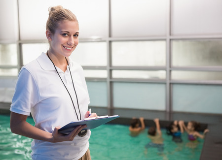 swimming pool woman: Pretty swimming coach smiling at camera at the leisure center