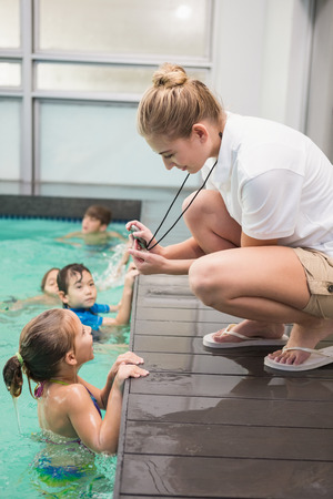 woman in water: Pretty swimming coach showing boy his time at the leisure center