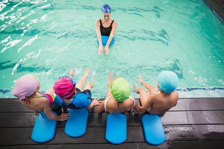 children learning: Cute swimming class watching the coach at the leisure center Stock Photo
