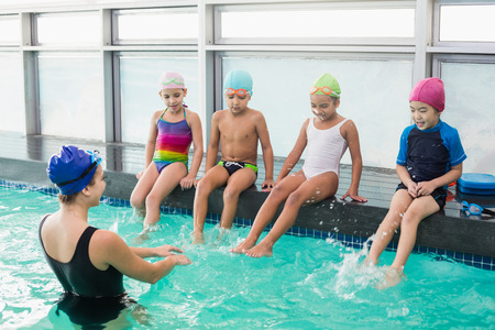 lesson: Cute swimming class watching the coach at the leisure center Stock Photo