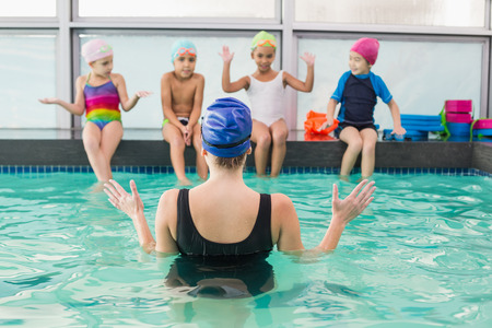 swimming pool woman: Cute swimming class watching the coach at the leisure center Stock Photo