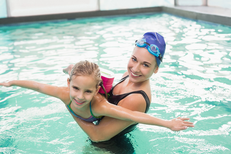 swimming pool woman: Cute little girl learning to swim with coach at the leisure center