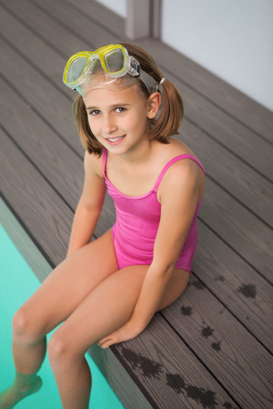 Cute little girl sitting poolside at the leisure center Stock Photo
