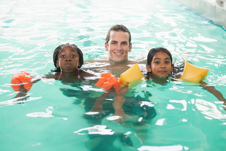 armbands: Cute swimming class in pool with coach at the leisure center Stock Photo