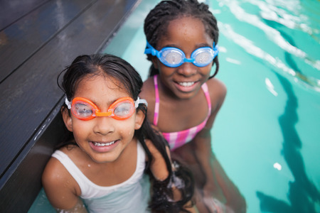 water black: Cute little kids sitting poolside at the leisure center Stock Photo