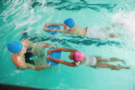swimming pool float: Cute swimming class in pool with coach at the leisure center Stock Photo