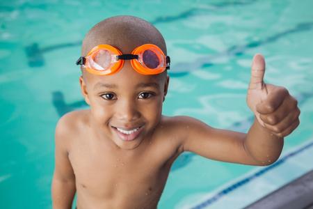Netter kleiner Junge, die Daumen nach oben am Pool im Freizeitzentrum