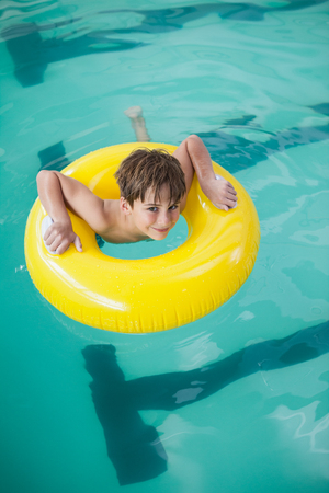 rubber ring: Little boy swimming with rubber ring at the leisure center