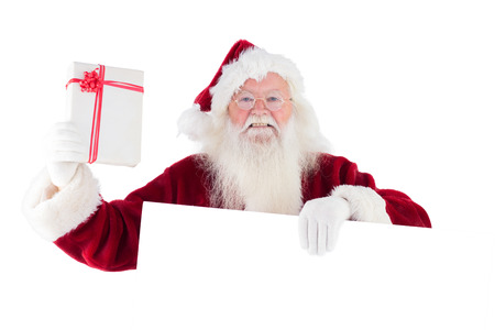 Santa shows a present while holding sign on white background photo