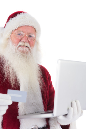 Santa pays with credit card on a laptop on white background photo