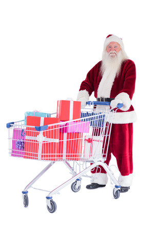 Santa pushes a shopping cart with presents on white background photo
