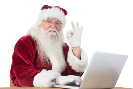 Santa is satisfied about what he found on his laptop, at the desk on white background photo
