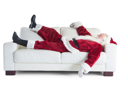 Father Christmas sleeps on a couch on white background Banque d'images