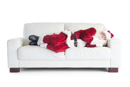 Father Christmas sleeps on a couch on white background Stock Photo