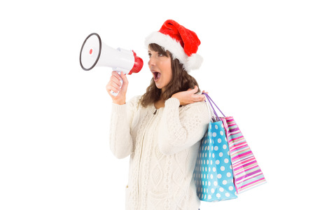 Festive brunette holding megaphone and bags on white background photo