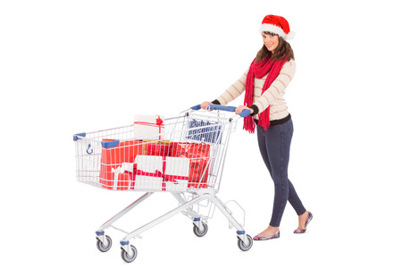 shopping trolley: Brunette in santa hat with shopping trolley on white background Stock Photo