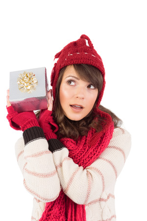 guess: Young woman shaking her gift in order to guess what it is on white background Stock Photo