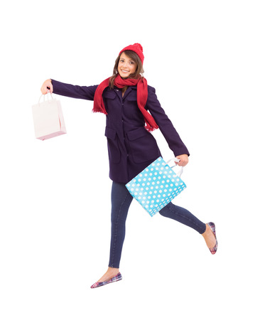 Festive brunette holding shopping bags on white background photo