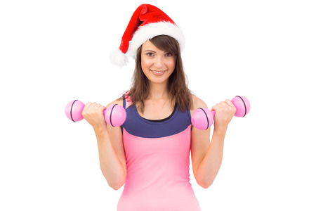 Woman in santa hat holding hand weight on white background photo