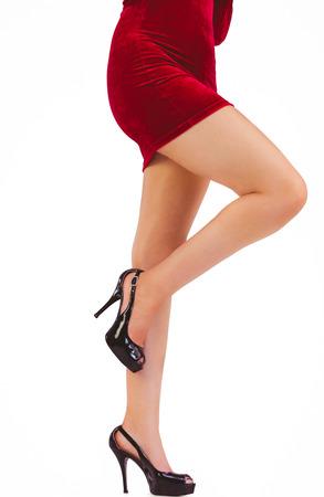 pere noel sexy: Womans festives jambes en talons hauts sur fond blanc