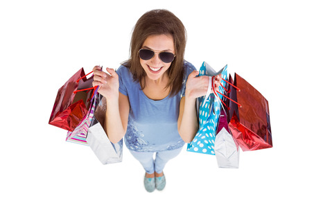 Happy brunette holding shopping bags on white background photo