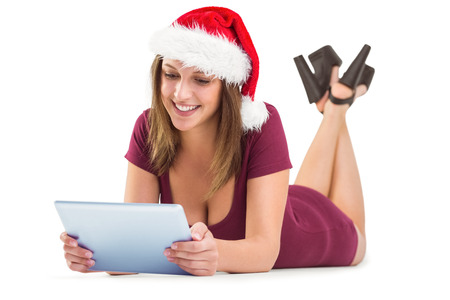 Festive brunette using tablet pc on white background photo