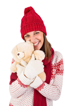 warm clothing: Cute brunette in warm clothing hugging teddy bear on white background Stock Photo