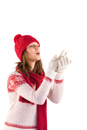 warm clothing: Woman in warm clothing blowing over hands on white background
