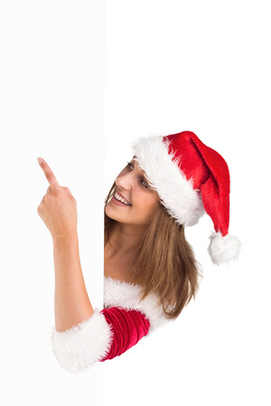Pretty girl in santa costume showing card on white background photo