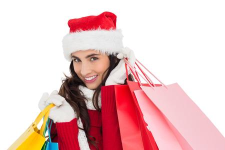 Festive brunette in winter wear holding shopping bags on white background photo