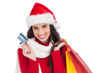 Excited brunette holding shopping bags and credit card on white background photo