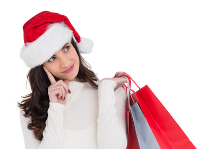 Festive brunette holding shopping bags and thinking on white background photo
