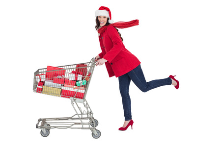 Festive brunette pushing trolley full of gifts on white background photo
