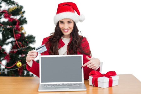 Festive brunette shopping online with laptop and pointing screen on white background photo