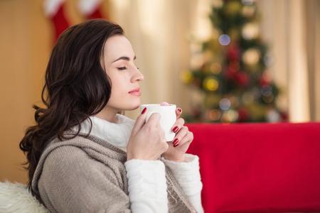 relajado: Morena disfrutando de un chocolate caliente en la Navidad en casa en la sala de estar Foto de archivo