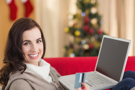 Brunette shopping online with laptop at christmas at home in the living room photo