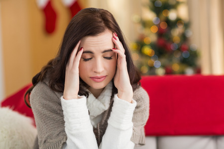woman headache: Brunette getting a headache on christmas day at home in the living room