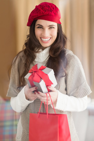 Happy brunette holding gift and shopping bags at home in the living room photo