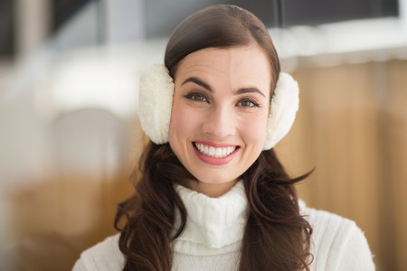 ear muffs: Beauty brunette with ear muffs smiling at camera at home