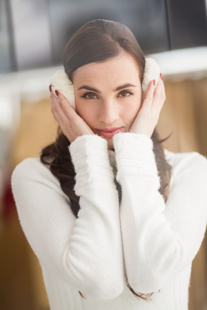 ear muffs: Pretty brunette with ear muffs at home Stock Photo