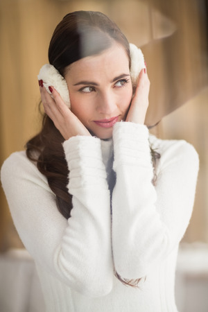 ear muffs: Pretty brunette with ear muffs thinking at home