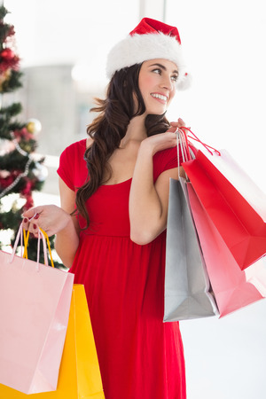 Brunette in red dress holding shopping bags at home in the living room photo