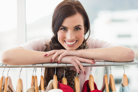 clothes rail: Smiling brunette smiling at camera by clothes rail at clothes store Stock Photo